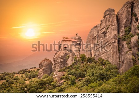 Holy Monastery of Saint Nicholas Anapausas in sunset at Meteora, Greece. Meteora are Orthodox 6 monasteries complex built on natural sandstone rock pillars. - stock photo