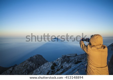 Holy mountain, Greece - May 17, 2016 :  Pilgrim takes picture of the shadow of the peak Athos over the sea.  Tourists  visit Holy mountain although women are not allowed to enter.