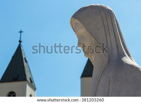 Holy Virgin Marry statue on blue sky, church tower in the background, Medugorje, Bosnia and Herzegovina - stock photo