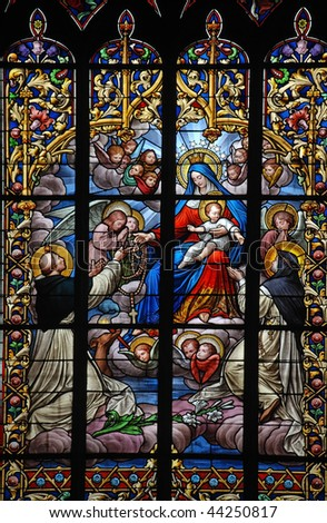 holy virgin Mary and Jesus receive a rosary from a saint on stained glass window in brittany