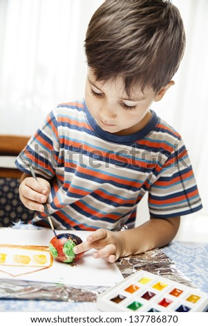 Home and family. Little boy draws house and easter egg with watercolor - stock photo