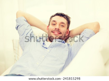 home and happiness concept - smiling man lying on sofa at home - stock photo