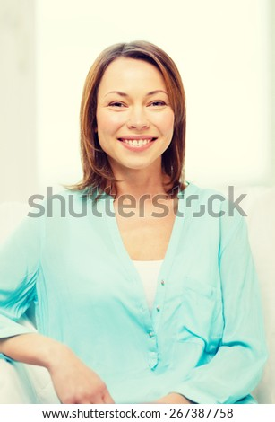home and happiness concept - smiling woman at home - stock photo