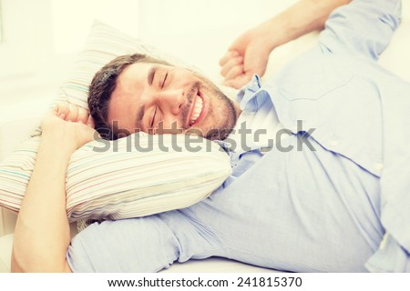 home and happiness concept - smiling young man lying on sofa at home - stock photo