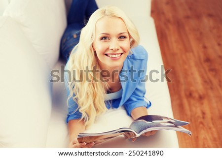 home and leasure concept - smiling woman lying on couch and reading magazine at home - stock photo