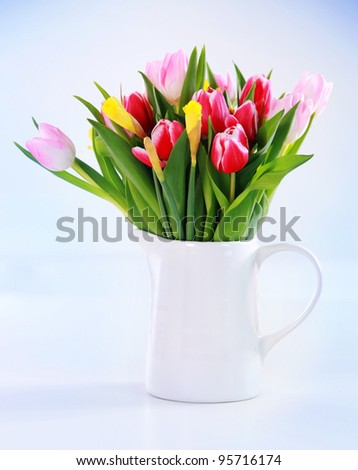 Home appliance - beautiful spring flowers in vase on the table - stock photo