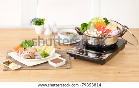 Home appliance electric aluminum sukiyaki cooking pot in the kitchen interior - stock photo