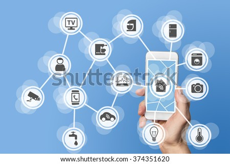 Home automation concept with hand holding modern smart phone to control home devices like a smart thermostat and sensor via the world wide web - stock photo