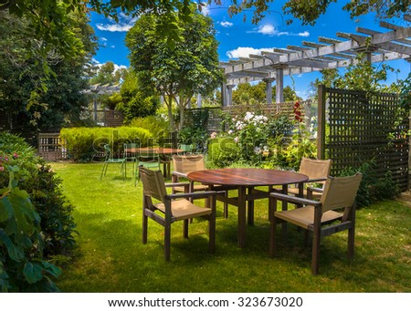 Home backyard with garden table set in sunny a lush garden with shade of trees - stock photo