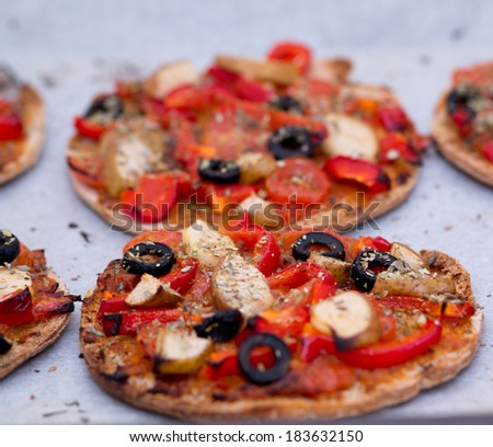 Home baked vegan mini pizza with olives, red pepper, tomato, pear, oregano and pesto on parchment paper - stock photo