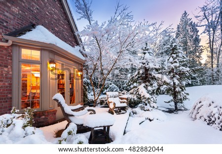 Home blanketed in snow as sun goes down on a winter evening