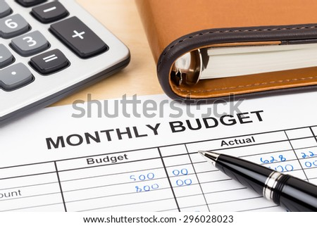 Home budget planning sheet with pen and calculator