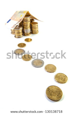 Home build with euro bank notes with a path made of coins - business concept - stock photo