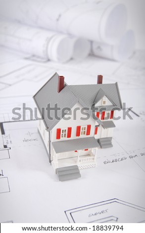 Home building concept shot with blueprints and small home model - stock photo