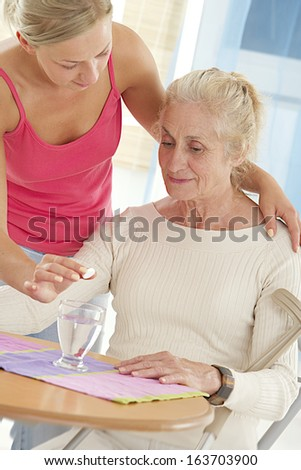 Home-care nurse helping elderly lady to take her painkiller - stock photo