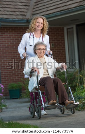 Home Care Nurse Pushing Senior on Wheelchair Outdoor in Early Morning - stock photo