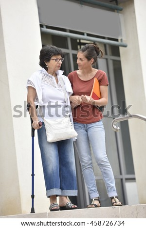 Home carer helping disabled woman getting down the stairs