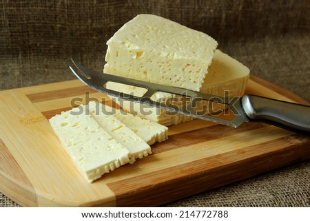 Home cheese, cut into pieces on the board and knife