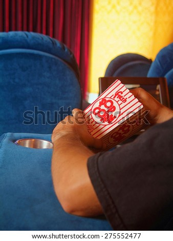 Home cinema, seat blue red curtain and man eat popcorn on the bucket, watch the movie at cinema. Entertainment movie nightlife, person watching film and eating popcorn on box.