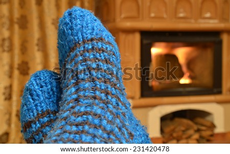Home comfort view to blue gross socks and fireplace. Feet in front of the fireplace symbolizing warmth of home. - stock photo