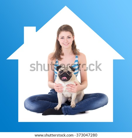 home concept - young beautiful woman holding pug dog in blue house frame - stock photo