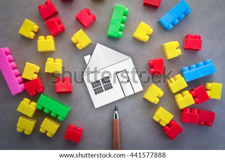 home construction concept with home paper cut and plastic model on grey background - stock photo