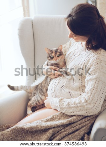 Home cozy portrait of pregnant woman resting at home on a chair