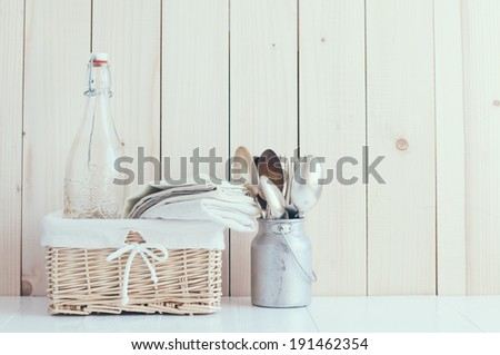 Home decor: glass bottle and wicker basket and vintage cutlery on a wooden board background, cozy kitchen arrangement in retro style, soft pastel colors. - stock photo