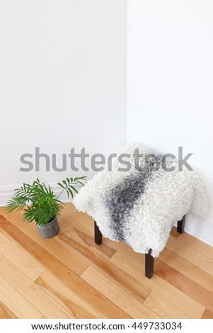 Home decor. Green plant and stool covered with sheepskin in the room corner. - stock photo