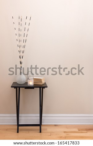 Home decor. Little table decorated with candlelight, vase and books.