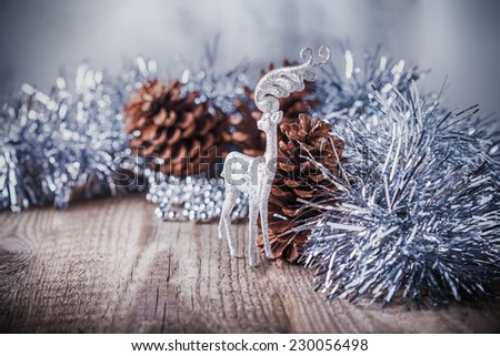 Home decor pine cones  and white deer on a wooden background.