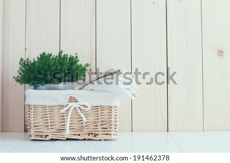 Home decor: vintage wicker basket, house plant and a stack of linen napkins on a wooden board  background, cozy composition retro style, soft pastel colors. - stock photo
