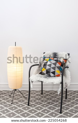 Home decorating. Chair with bright cushion and elegant floor lamp. - stock photo