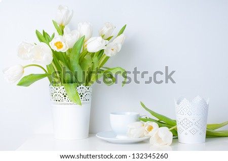 Home decoration, fresh white tulips in a vase and a cup on a white table, close-up - stock photo