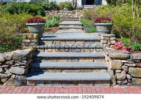 Home entrance walkway, stone wall, bluestone steps and big planters - stock photo
