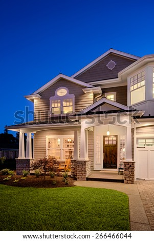 Home Exterior at Night: Beautiful Luxury House after Sunset with Deep Blue Sky, Green Lawn, Gables, Covered Porch, and Garage - stock photo