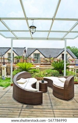 Home exterior patio with wooden decking and rattan sofa  - stock photo