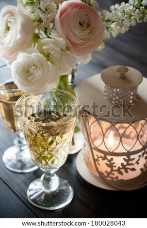 Home festive wedding decor, exquisite bouquet of flowers, buttercups and white lilacs, two wineglasses and lantern candle on a dark wooden board
