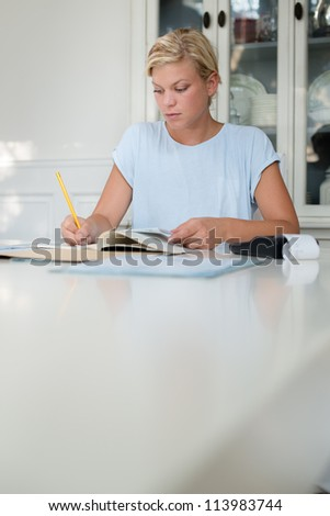 Home finance, personal savings, and financial planning, young caucasian woman checking bills and doing budget with calculator and papers - stock photo
