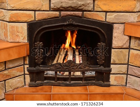 Home fireplace, burning logs, cozy atmosphere - stock photo