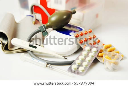 Home first aid kit with different medical devices and pills on light background