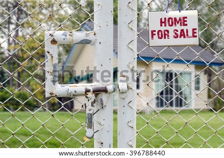 Home For Sale and Real Estate Sign on wire mesh fence - stock photo