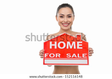 Home for sale. Beautiful naked woman holding a home for sale sign while isolated on white