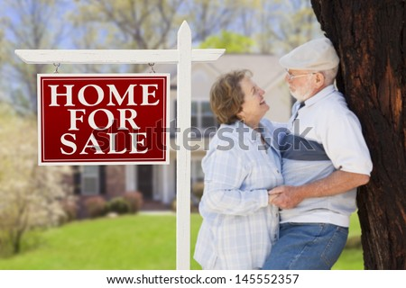Home For Sale Real Estate Sign with Happy Affectionate Senior Couple Hugging in Front of House.