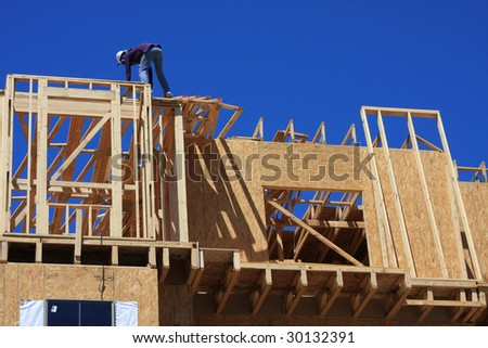 Home frame with construction worker present - stock photo