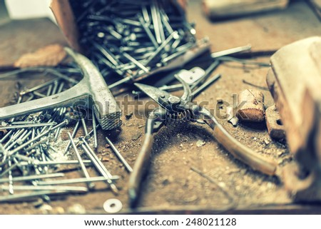 Home garden tools with industrial scissors, hammer, nails and other tools in workshop - stock photo