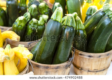 Home grown zucchini in brown bushel baskets sitting on table at farmers market