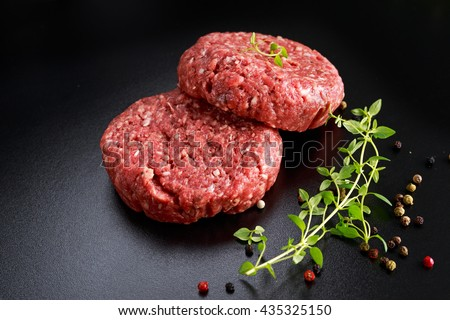 Home HandMade Raw Minced Beef steak burgers on black board - stock photo