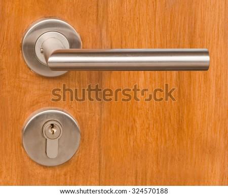 Home Hardware, Close Up of Lock and Door Handle Knob on Brown Wooden Door. - stock photo