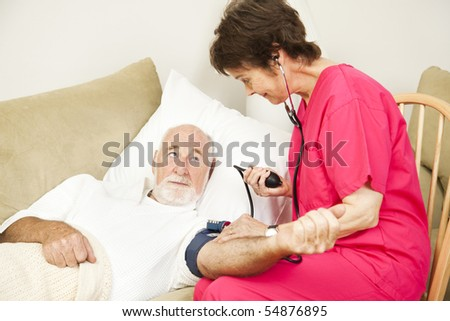 Home health care nurse taking a senior patient's blood pressure. - stock photo